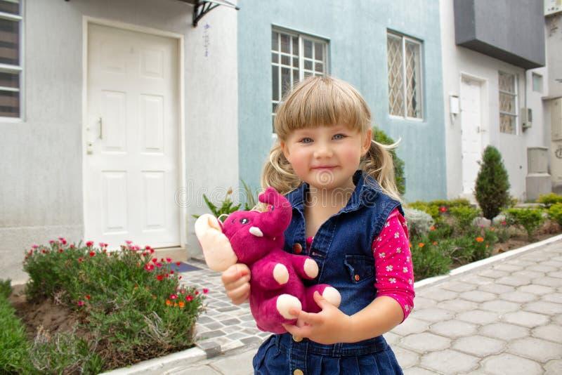 La petite belle fille marche avec un jouet mou dans leurs mains sur l'air ouvert photo libre de droits