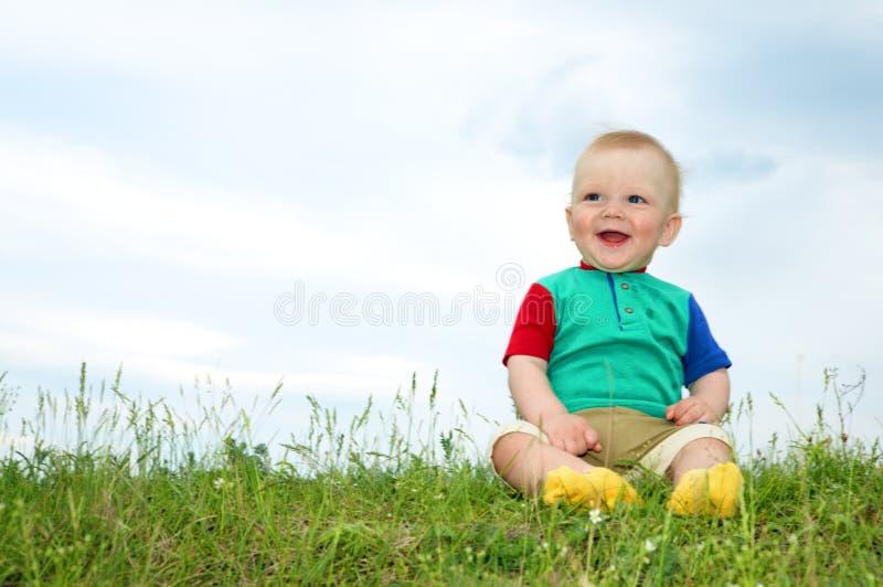 La petite chéri s'asseyent sur l'herbe verte photo libre de droits