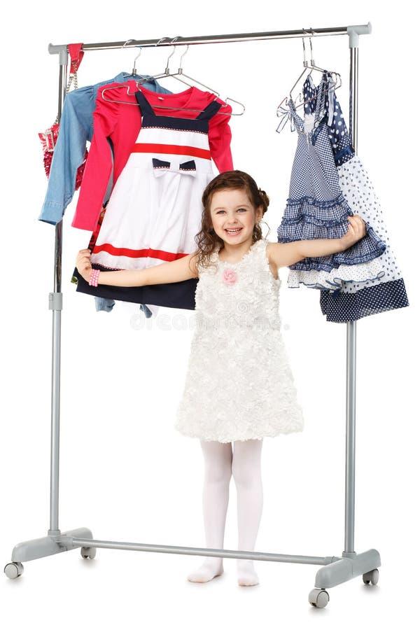 La petite fille à la mode choisit des vêtements dans une garde-robe photo libre de droits