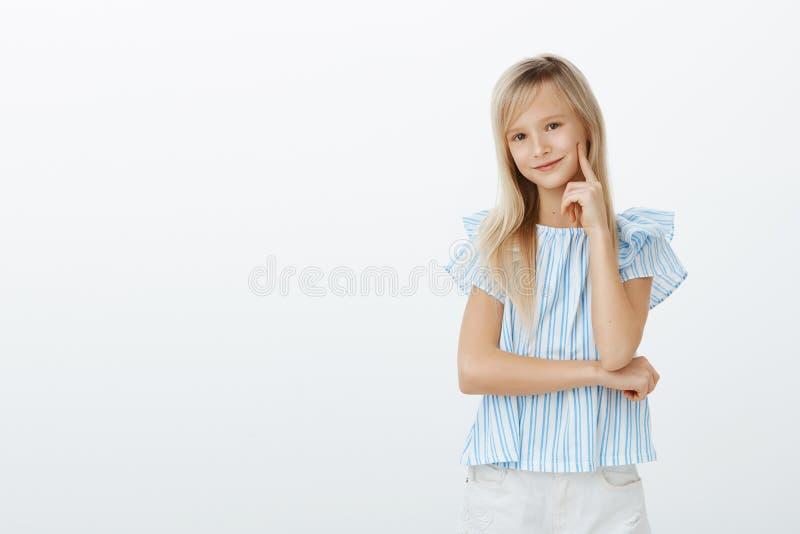 La petite fille à la mode connaît tout au sujet des robes mignonnes Enfant émotif heureux heureux avec les cheveux blonds, tenant photo stock