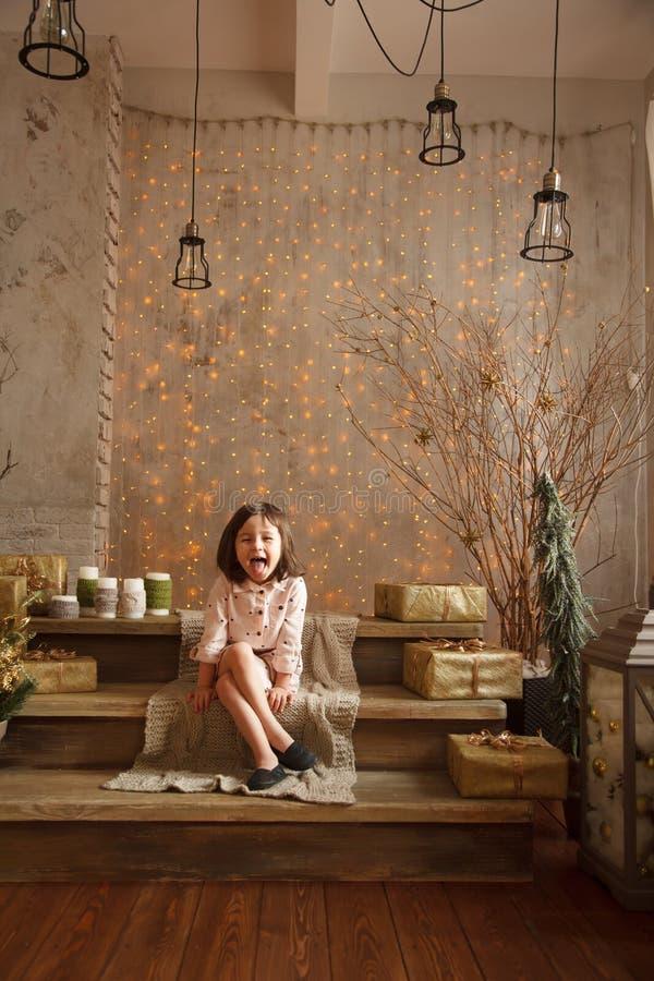 La petite fille élégante dans les décorations de Noël montre son tongu photo libre de droits