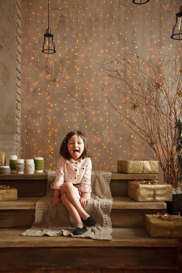 La petite fille élégante dans les décorations de Noël montre son tongu photographie stock libre de droits