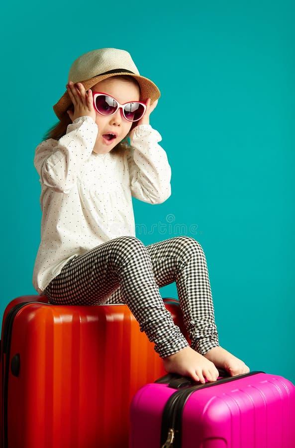 La petite fille étonnée s'assied sur des valises, exprime la joie sincère, a mis des mains pour faire face, démontre l'émotion po images libres de droits