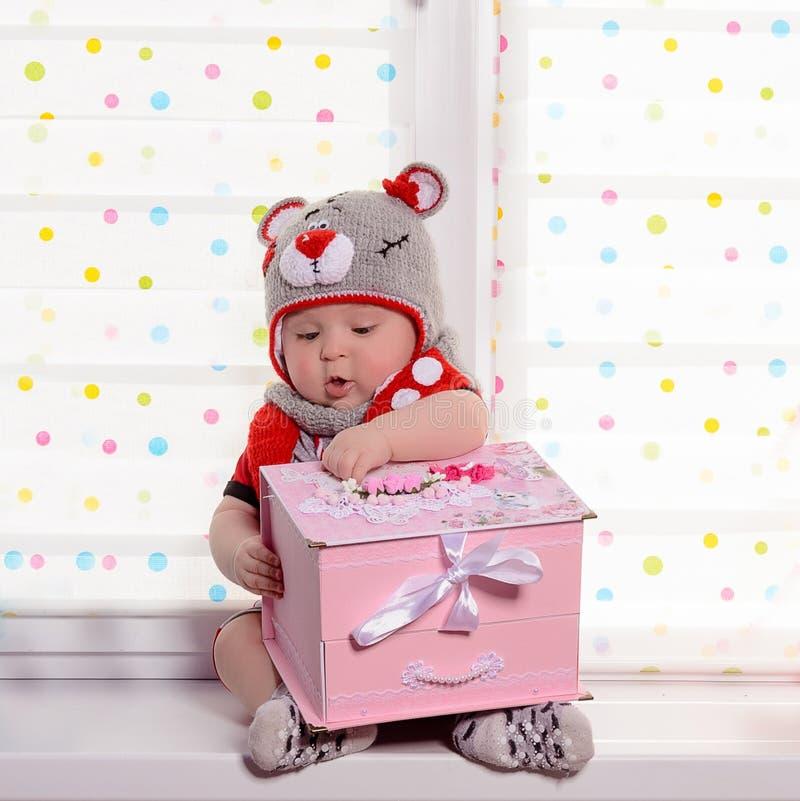 La petite fille étonnante s'assied sur la fenêtre et regarde le cadeau reçu image stock