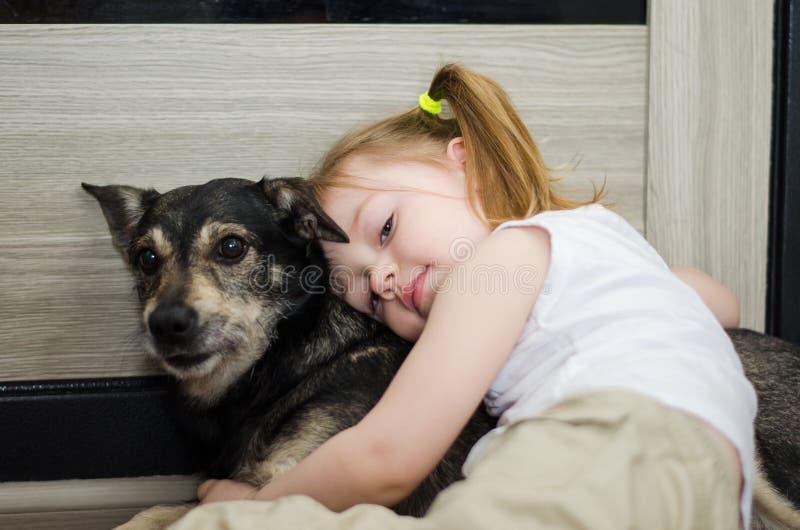 La petite fille étreint son chien photographie stock