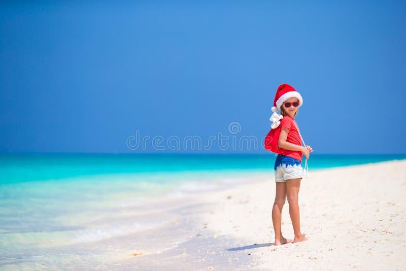 La petite fille adorable dans le chapeau de Santa et un sac avec des cadeaux pendant le Noël échouent des vacances images stock