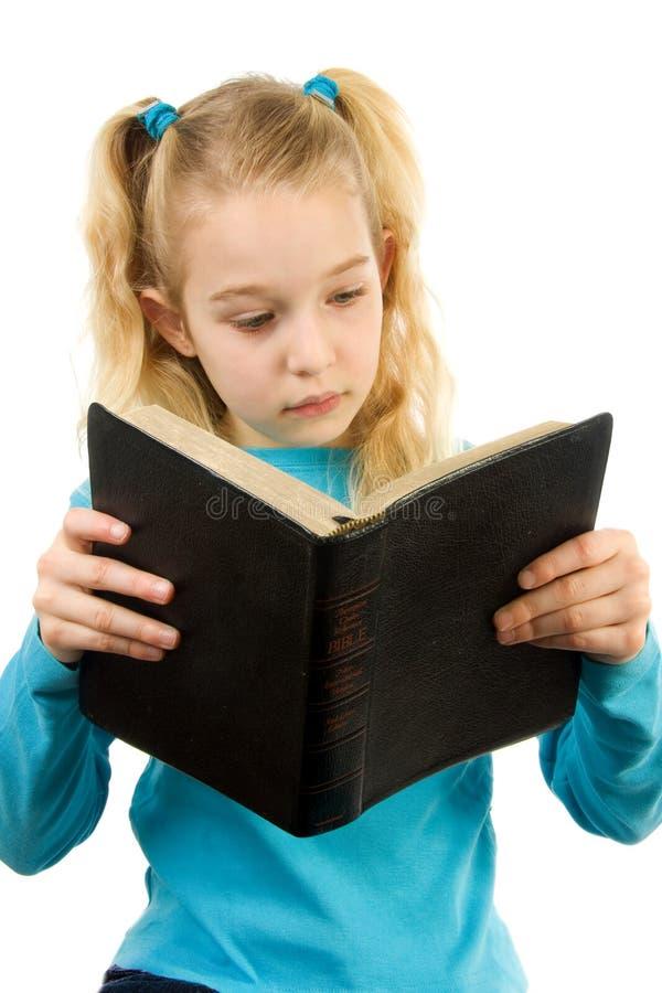 La petite fille affiche la bible image stock