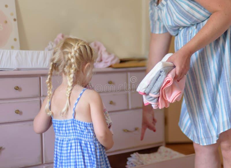 La petite fille aidant la maman enceinte a mis la blanchisserie propre dans le dresse photo stock