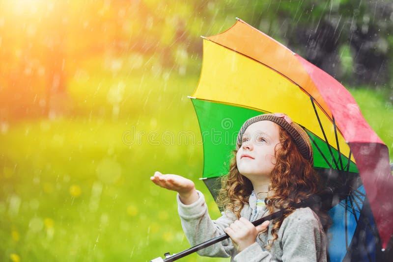 La petite fille apprécient à la pluie de ressort photographie stock