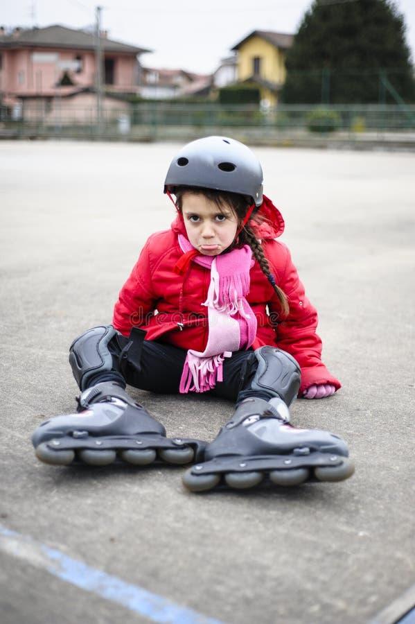 La petite fille apprend à patiner avec le roller au basket-ball photographie stock libre de droits