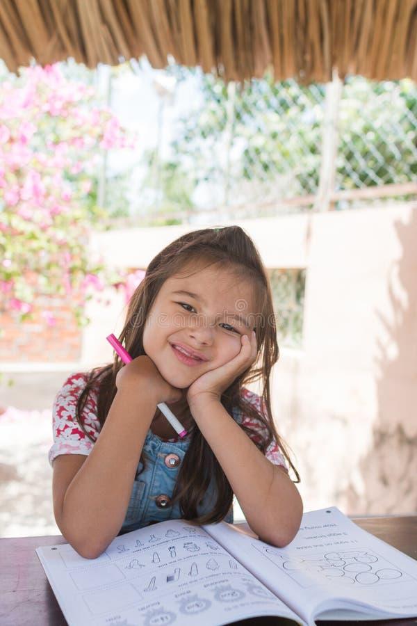 La petite fille apprennent le livre avec des mathematicks, elle est perdue dans la pensée et ennuyée photo stock