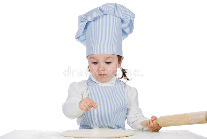 La petite fille arrosent la farine sur la pâte de pizza photo stock