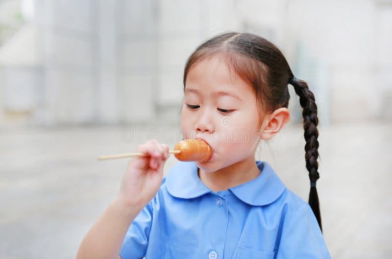 La petite fille asiatique adorable d'enfant dans l'uniforme scolaire ont plaisir à manger la saucisse photos stock