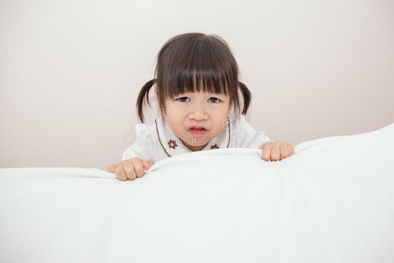 La petite fille asiatique adorable se réveillent dans son lit photographie stock