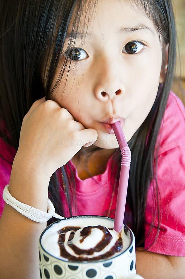La petite fille asiatique apprécient une cuvette de secousse de chocolat. images libres de droits