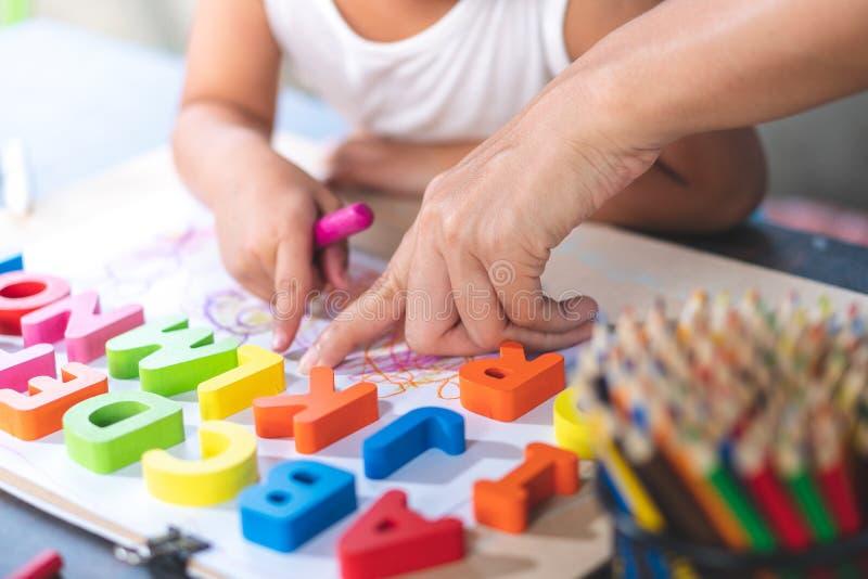 La petite fille asiatique apprend les lettres anglaises photos stock