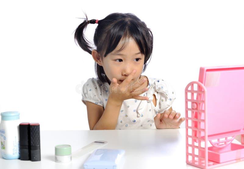 La petite fille asiatique de sourire s'applique composent la poudre de bébé son fa image stock