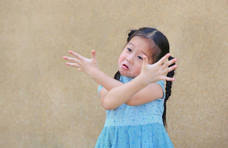 La petite fille asiatique impertinente d'enfant avec le visage drôle et l'expression croisent son bras photographie stock