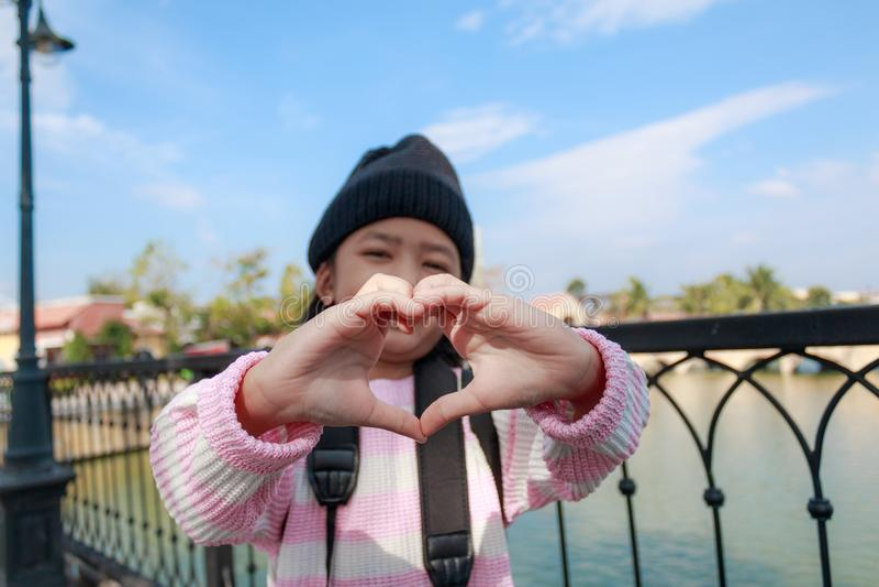 La petite fille asiatique montrant la main font la forme de coeur avec bonheur i photo stock