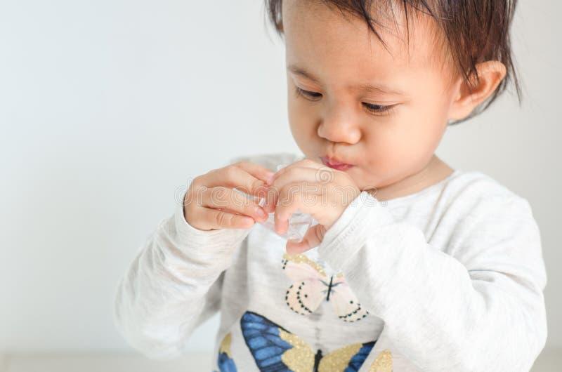 La petite fille asiatique prend le sirop de médecine seule images libres de droits