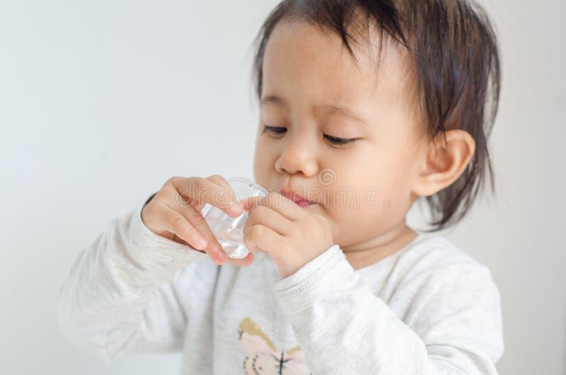 La petite fille asiatique prend le sirop de médecine seule photos libres de droits
