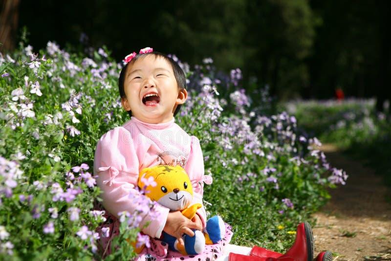 La petite fille asiatique rit image stock