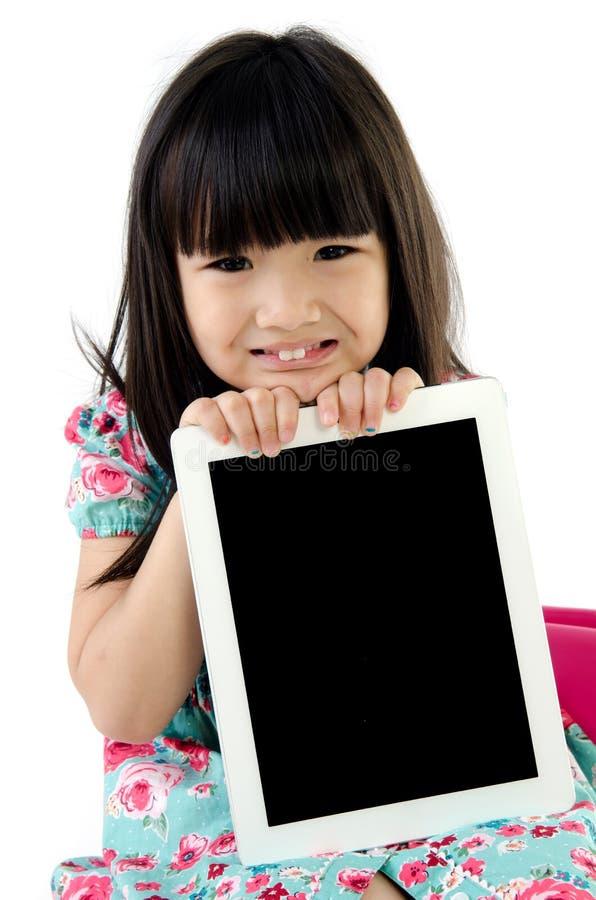 La petite fille asiatique sourit avec la tablette photos libres de droits