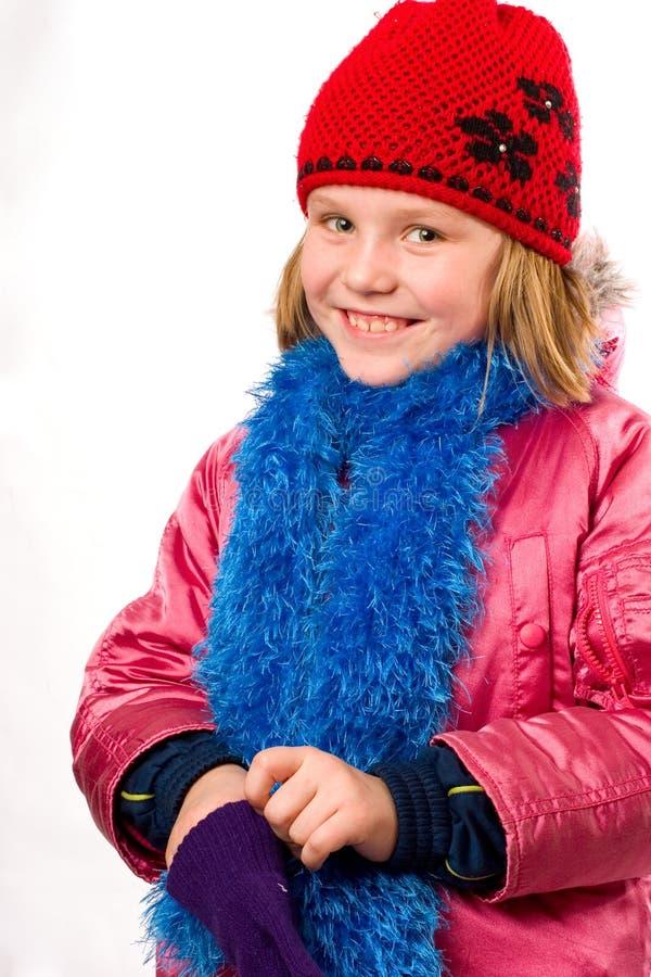 La petite fille assez joyeuse a rectifié des vêtements de l'hiver i image libre de droits