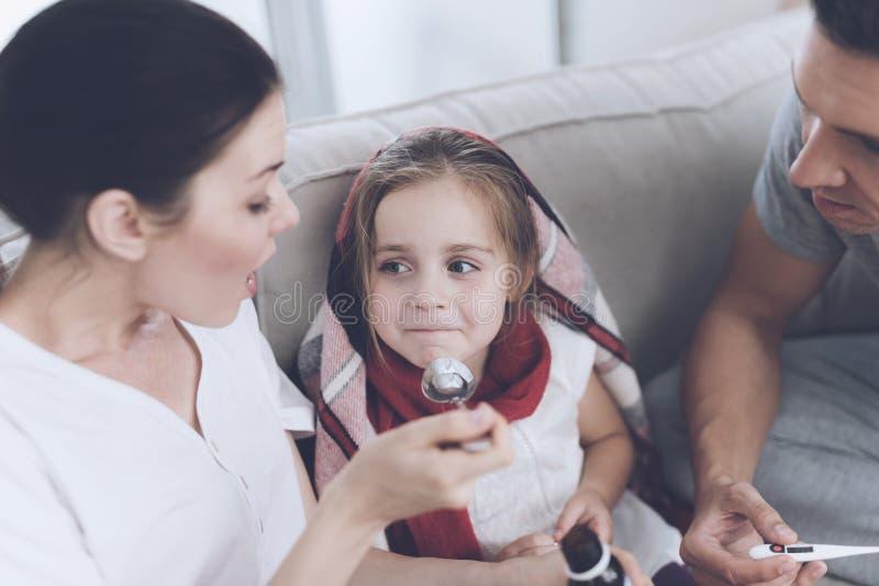 La petite fille a attrapé froid Sa mère et père la traitent La mère verse un sirop de fille dans une cuillère images stock