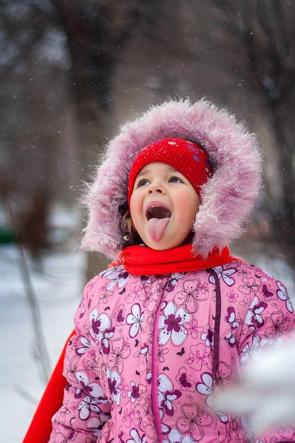 La petite fille attrape une bouche de flocon de neige sur la promenade en parc images libres de droits