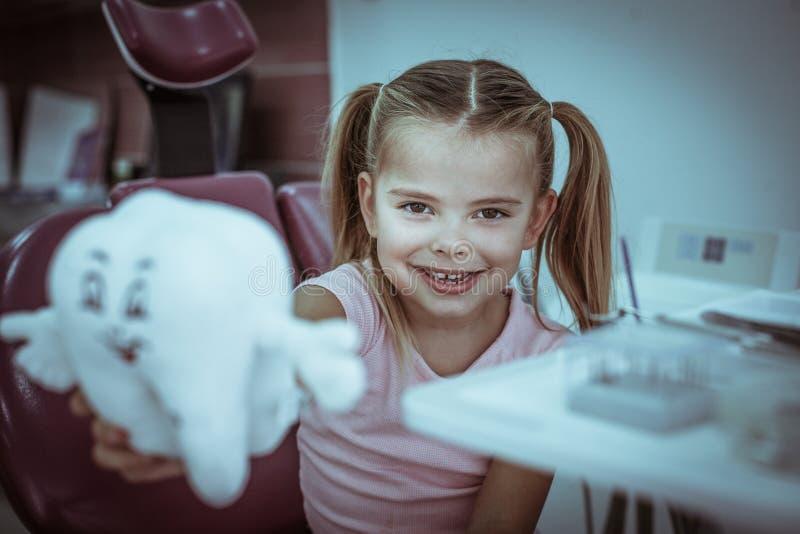 La petite fille au bureau de dentiste pose avec le jouet de dents image libre de droits