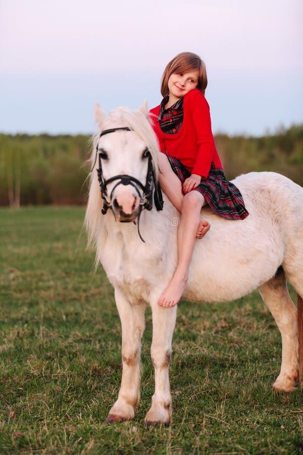 La petite fille aux pieds nus de jeune dame s'asseyant sur un poney et lancent image libre de droits