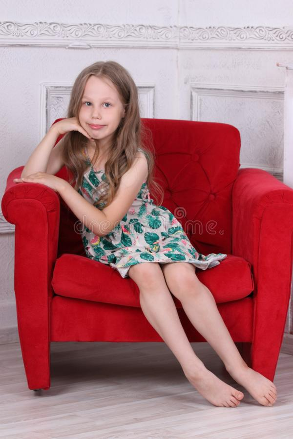 La petite fille aux pieds nus heureuse dans la robe s'assied photographie stock