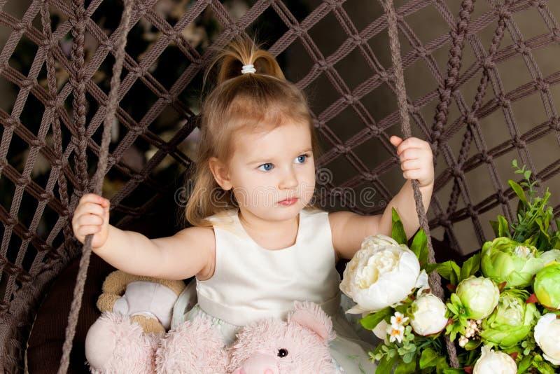 La petite fille aux yeux bleus blonde s'asseyant sur un knit d'oscillation photos stock