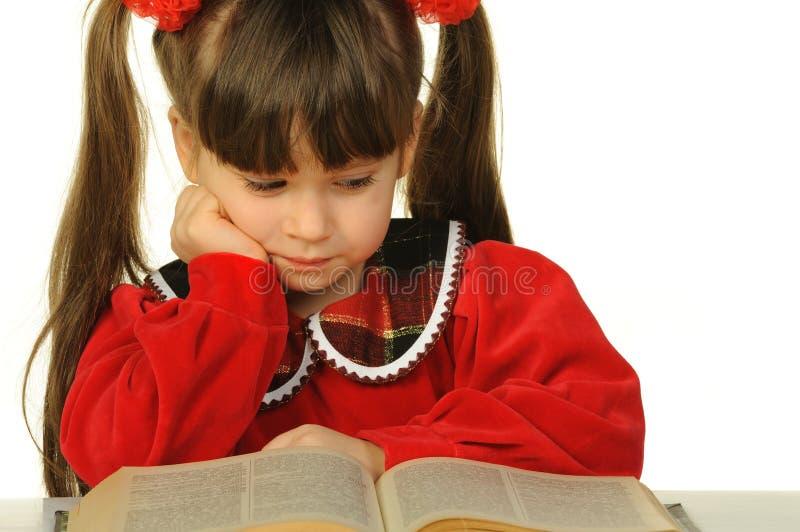 La petite fille avant le grand livre scientifique photographie stock libre de droits