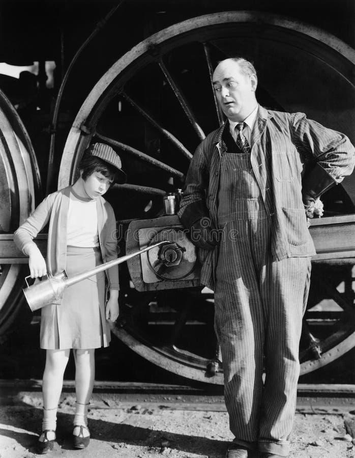 La petite fille avec de l'huile peut se tenant à côté d'une locomotive et du conducteur de moteur (toutes les personnes représent images libres de droits