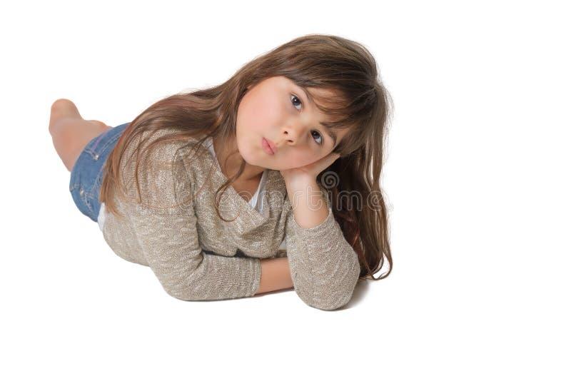 La petite fille avec des lèvres de crachement se trouve sur le fond gris photographie stock