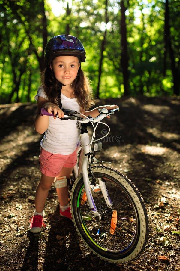 La petite fille avec la bicyclette en été se garent dehors image libre de droits