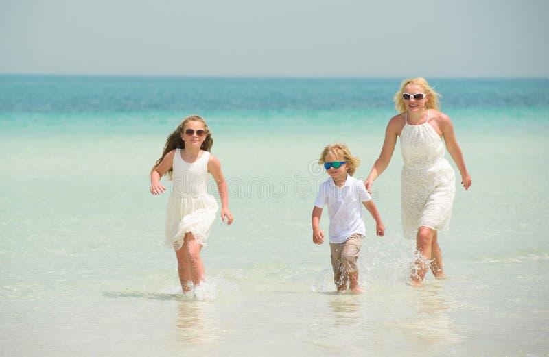 La petite fille avec la famille a l'amusement à la plage photo libre de droits