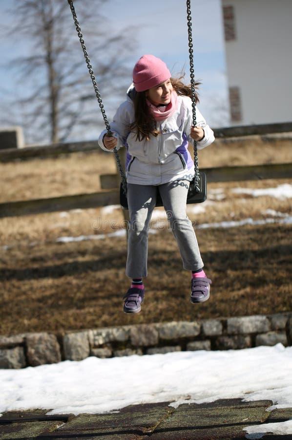 La petite fille avec le chapeau rose de laine a l'amusement sur l'oscillation dans le playg photos stock