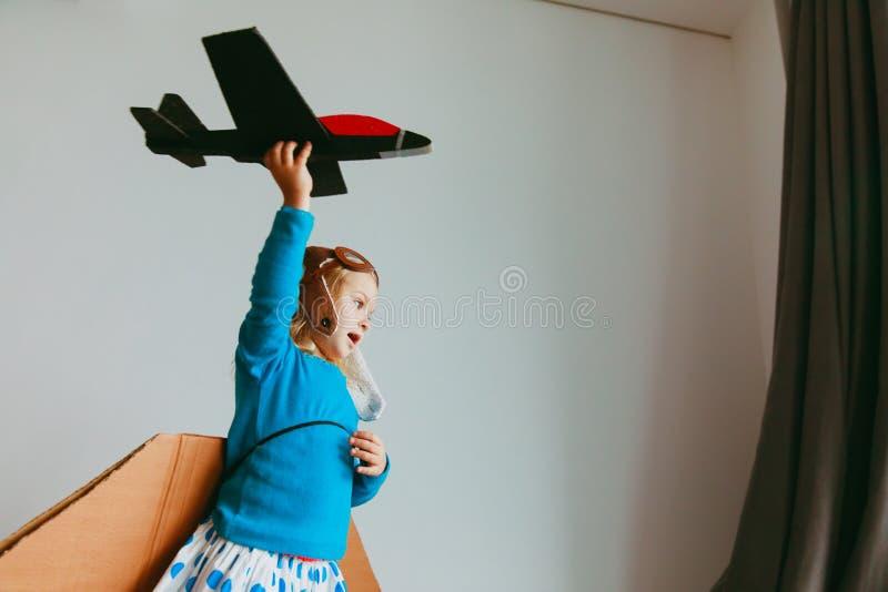 La petite fille avec le jeu pilote en verre et d'ailes volent à la maison image libre de droits