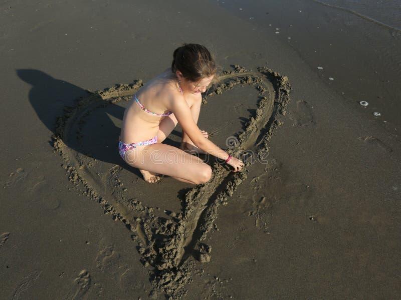 La petite fille avec le maillot de bain dessine un grand coeur sur le sable humide images stock