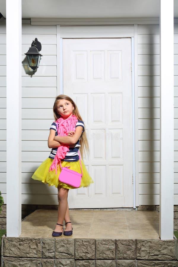 La petite fille avec le sac à main se tient sur le porche blanc de la maison images libres de droits