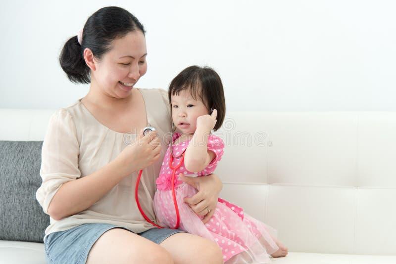 La petite fille avec sa mère a joué dans les médecins images stock