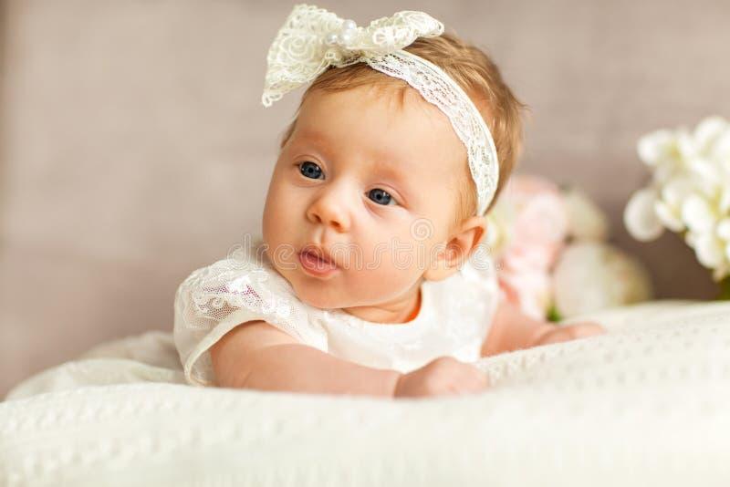 La petite fille avec un arc blanc se trouve sur le divan, sur un backg blanc photographie stock