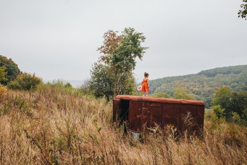 La petite fille avec une poupée se tient sur la vieille remorque dans les bois photo libre de droits