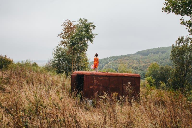 La petite fille avec une poupée se tient sur la vieille remorque dans les bois photographie stock libre de droits