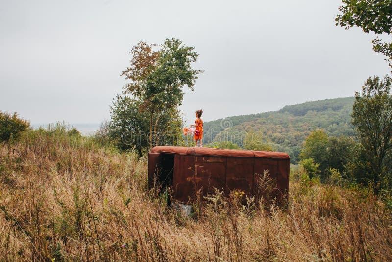 La petite fille avec une poupée se tient sur la vieille remorque dans les bois photo stock
