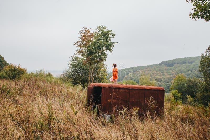 La petite fille avec une poupée se tient sur la vieille remorque dans les bois image stock