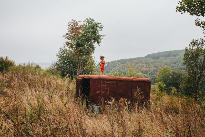 La petite fille avec une poupée se tient sur la vieille remorque dans les bois photos stock